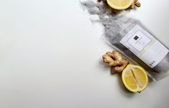 this photo shows the Detox 300mg bath salt in its package with ginger and lemon beside it representing it's fragrance oils